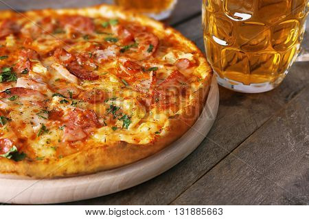 Delicious pizza  and glasses of beer are on wooden table, close up