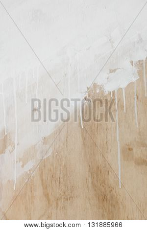 Textured wooden background with dripping white paint