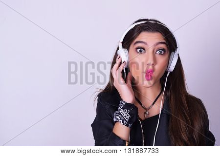 Music. Young hispanic woman listening to music with headphones. Playful woman isolated over grey background doing fun expression.