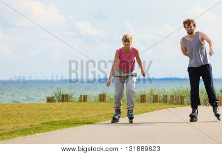 Love romance sport fitness leisure concept. Teen couple together on skates. Girl and boy riding rollerskates in coastal park.