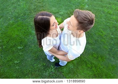 Loving couple on green grass background