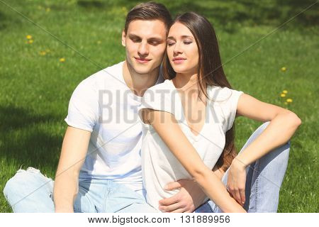 Young loving couple on green grass background