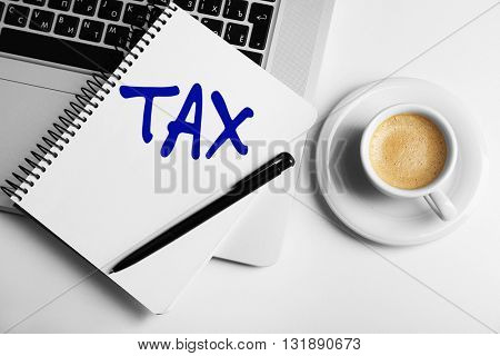 Tax Concept. Notebook on laptop keyboard, on light background