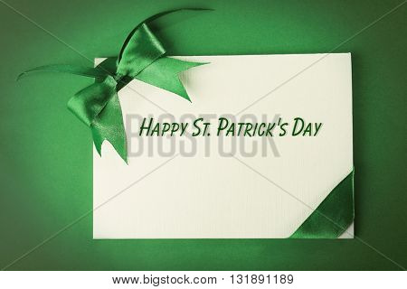 Card decorated with green bow on green background. Happy St. Patrick's Day