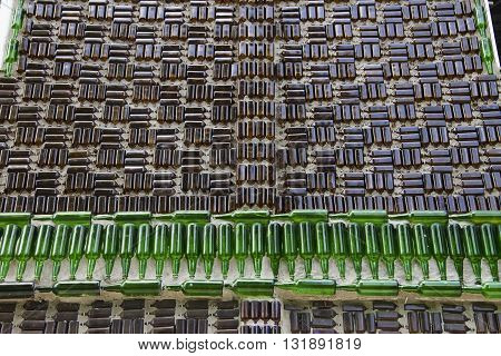 A bunch of green and brown glass bottles glued on the wall.