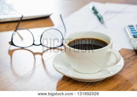 Cup of coffee galsses and Office Supplies on wooden table