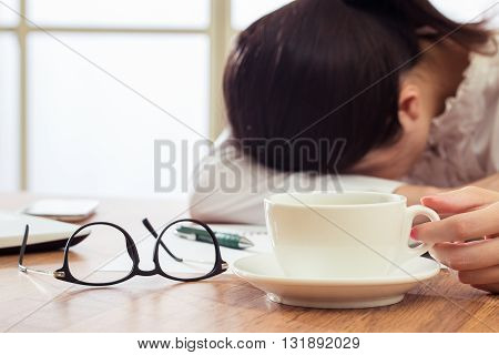 Exhausted And Tired Young Businesswoman Sleeping On Desk