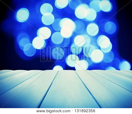 Wooden board against blue lights background