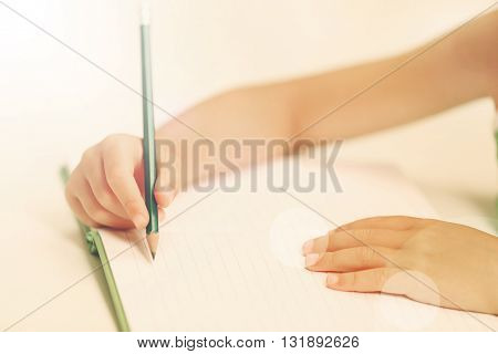Children hand with pencil writing on notebook