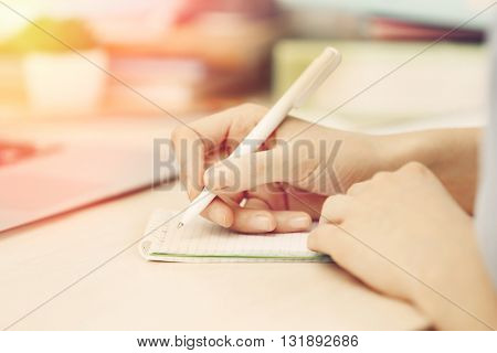 Femaale hand with pen writing on notebook