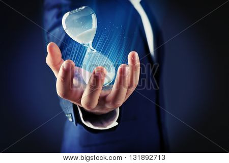 Businessman holding hourglass in hand on dark background