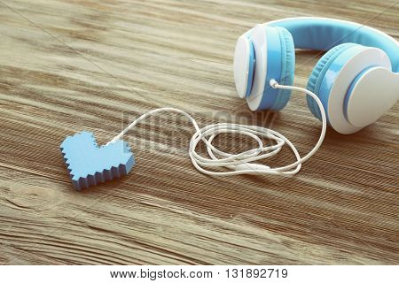 Blue headphones with heart on wooden background