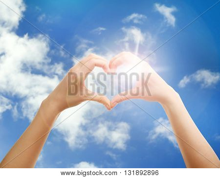 Hands in shape of love heart on blue sky with sun
