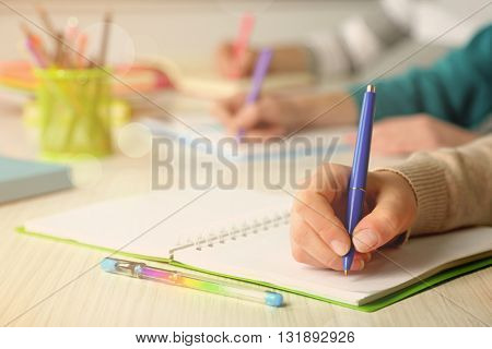 Students hands with pen writing on notebook