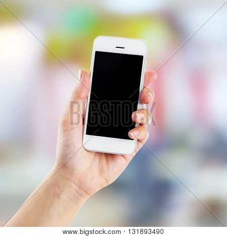 Hand shows mobile smart phone, blurred background