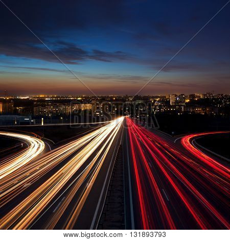 Speed Traffic at night  in the city - light trails on motorway highway at dusk,  long exposure, urban background with illumination