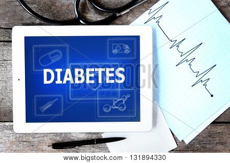 Medical tablet and text Diabetes on screen on wooden table
