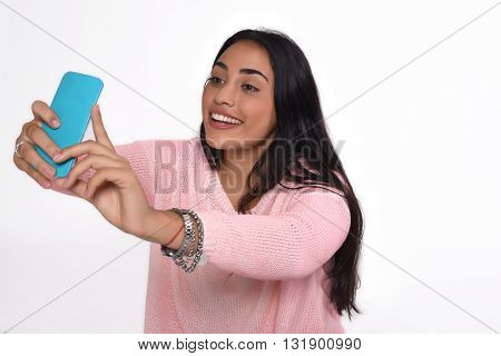 Young beautiful woman taking selfie with smartphone indoor. Isolated white background.