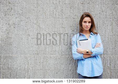 Half length portrait of hipster girl with portable digital tablet in hands is posing for camera against street wall background with copy space for your advertising text message or promotional content
