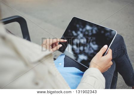 Closely image of hipster girl is chatting in social network via touch pad while is relaxing in the fresh air during free time.Top view of woman`s hand is holding digital tablet with copy space screen