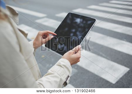 Closely of business person is using banking application via digital tablet while is waiting on the street car with clients. Close up woman is checking e-mail on touch pad with blank copy space screen