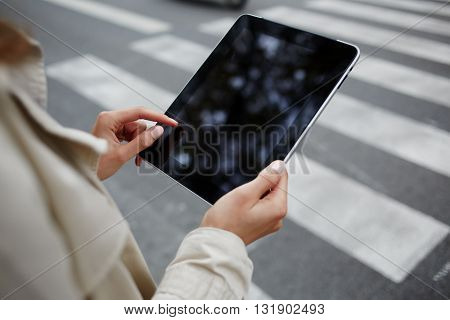 Closeup of businesswoman is reading e-mail on her touch pad while is waiting car on the street . Closely of female is working on digital tablet with empty copy space screen for advertising content