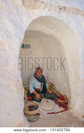 HAMMAMET TUNISIA - Oct 2014: Woman is grinding grain in berber house on October 7 2014 in Hammamet Tunisia