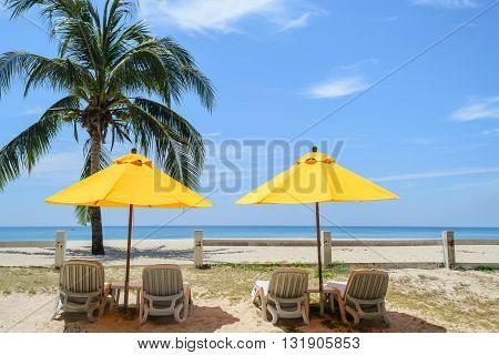 Beach chairs and Yellow Umbrellas on the Bang Tao beach Phuket in Thailand