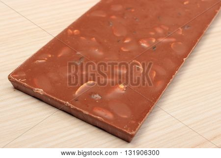 Whole nutritious chocolate with nuts and raisins on wooden table
