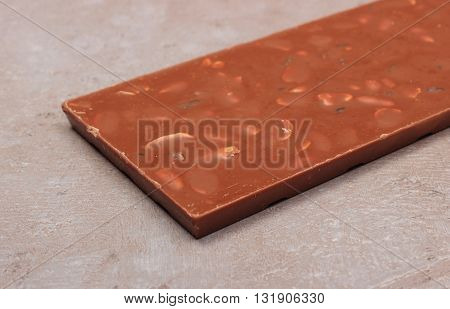 Whole nutritious chocolate with nuts and raisins on structure of gray concrete
