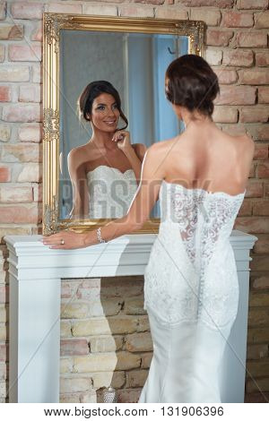 Beautiful young bride looking at herself in mirror, smiling happy.