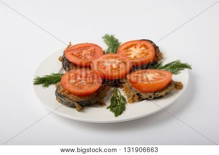 Baked eggplant with tomatoes on a white plate