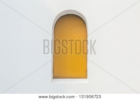 Yellow round arch window and white wall