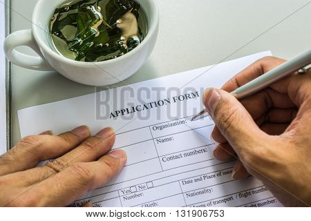 application form with tea cup.hand man Filling in the application form in black ink