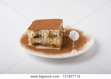 Piece of tiramisu cake on white plate