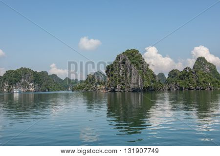 Scenic view of the large limestone karsts formation on Ha Long Bay in Vietnam. Lush greeneries cover the limestone karsts like a blanket and looks gorgeous. It's a UNESCO heritage site.