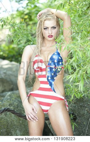A gorgeous young fit and petite blonde with wet hair looking at the camera while wearing an American flag one piece swimsuit with rocks and trees in the background on a sunny day.