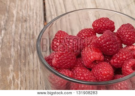 Clear glass bowl of ripe raspberries on a rustic farm picnic table in summer.