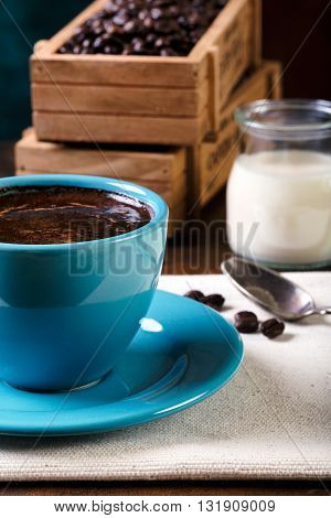 Cup Of Coffee And Wooden Containers Filled With Cofee Beans