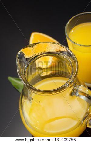 orange juice and fruit on black background