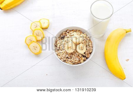 Granola bananas and a glass of milk on a light wooden surface. Healthy food