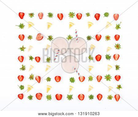 Three strawberry smoothie on a white background with strawberry slices. Top view. Flat lay