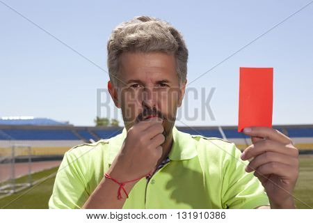 Angry football referee blowing a whistle and pointing with his hand