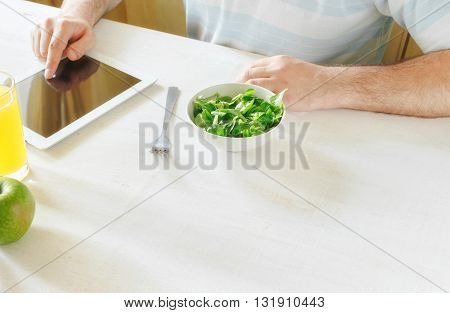 Healthy lifestyle concept. Man eating salad while sitting at a white table home