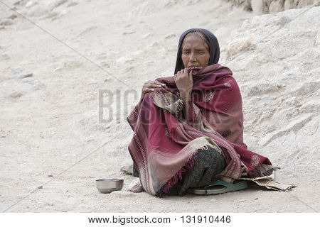 LEH INDIA - JUNE 24 2015: Unknown poor woman begs for money from a passerby on the street in Leh Ladakh. Poverty is a major issue in India