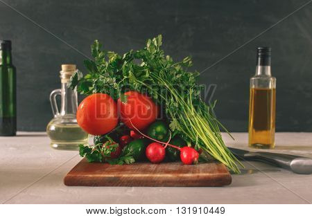 Set of vegetables on white table on a black background. Branch tomatoes bunch of parsley radishes and cucumbers. Helpful and diet food.
