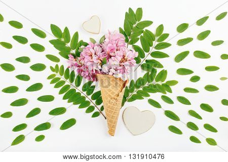Cone with acacia flowers in acacia leaves with small wooden hearts on white background. Top view. Flat lay