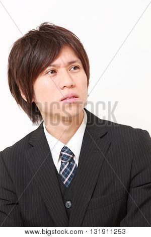 portrait of young Japanese businessman worries about something on white background