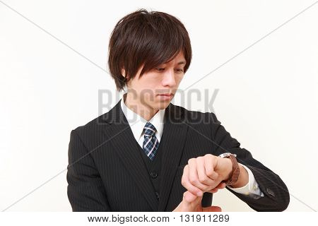 portrait of businessman checking time on his watch on white background