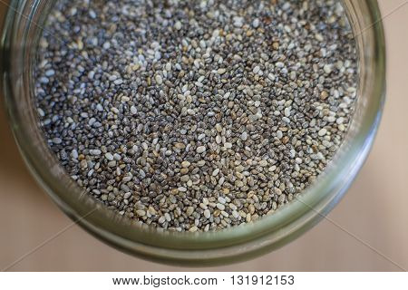 Glass jar with chia seeds over wooden surface. Selective focus. High angle view